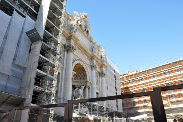 All you'll get at the moment is a glimpse of the Trevi Fountain as it's being extensively renovated.  Save your coin for another time.